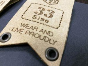 Etichetta in Alcantara, stampata a caldo e ricamata con impuntura di filo.